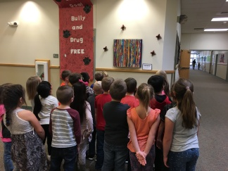 Art piece created by first grade students and students admiring their art.