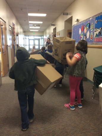 Students delivering boxes and charting progress on a graph